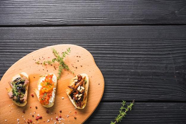 Bocadillos de tostadas con tomillo y semillas de granos de pimienta roja en una tabla de cortar Foto gratis