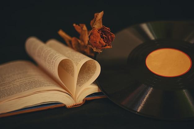 Bodegón con libros en forma de corazón, flores secas y cd antiguo. Foto gratis