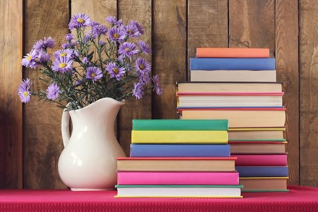 Bodegón con libros y un ramo otoñal contra tablas. Foto Premium