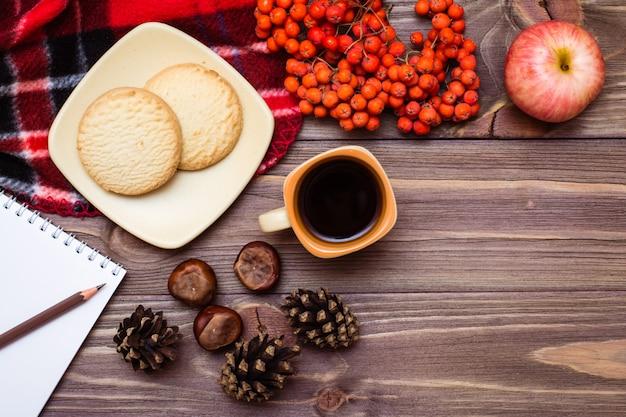 Bodegón otoñal: café, galletas, una tela escocesa, un cuaderno y un lápiz sobre madera Foto Premium