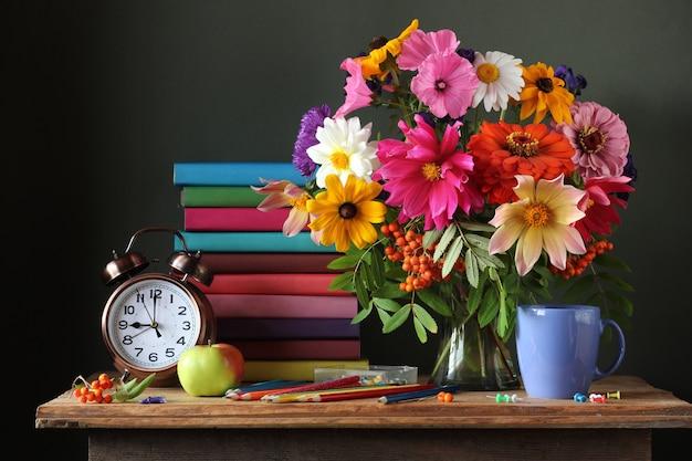 Bodegón con ramo otoñal, despertador y libros. educación. Foto Premium