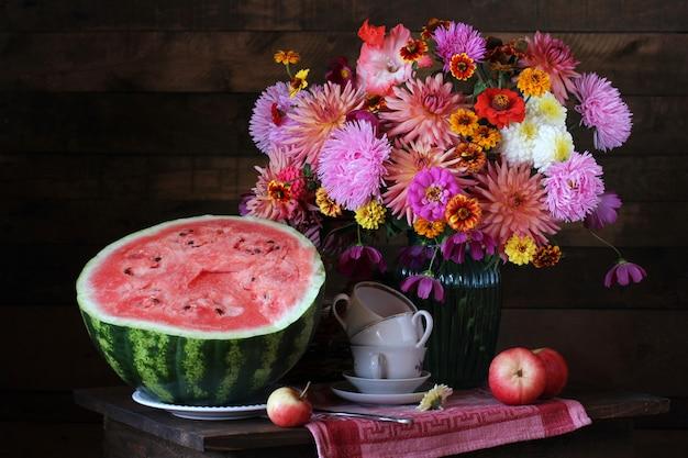 Bodegón con ramo y sandía. asters, dalias y diferentes flores de otoño en un jarrón. Foto Premium