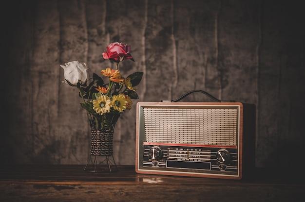 Bodegón con un receptor de radio retro y floreros Foto gratis