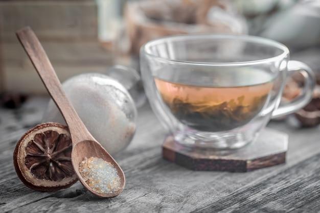 Bodegón con taza de té transparente y fragante con jengibre sobre fondo de madera Foto Premium