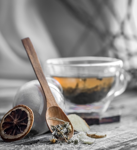 Bodegón con taza de té transparente y fragante con jengibre sobre fondo de madera Foto gratis