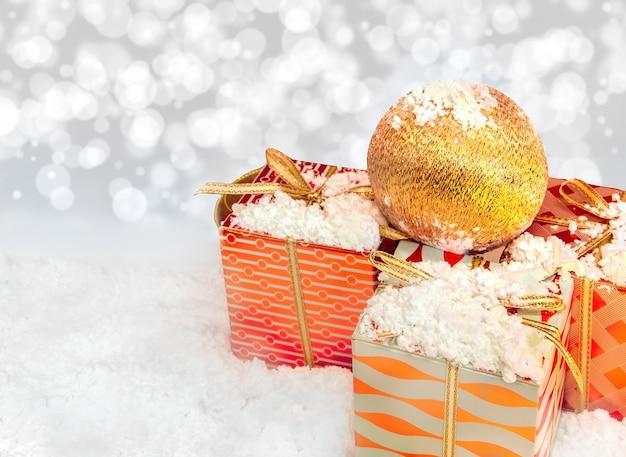 Bola de navidad sobre regalos con nieve descargar fotos - Bola de navidad con foto ...