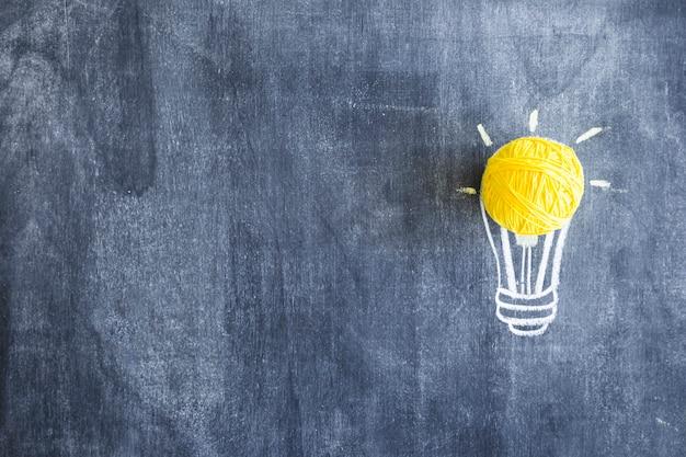 Bola de lana amarilla sobre la bombilla dibujada a mano en la pizarra Foto gratis