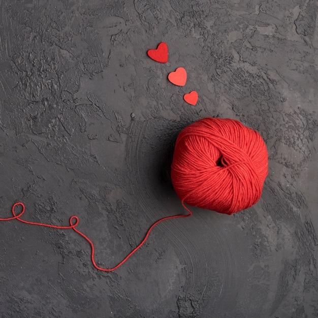 Bola de lana roja sobre fondo de pizarra Foto gratis
