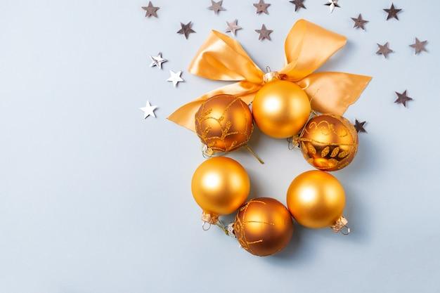 Bola de navidad dorada y amarilla con cinta sobre fondo azul con estrellas plateadas Foto Premium