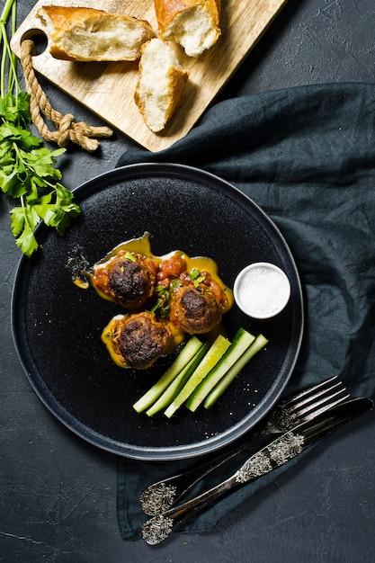 Bolas de carne en salsa de tomate en un plato negro, pepinos, sal, pan. Foto Premium
