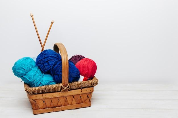 Bolas de lana azules y rojos en cesta Foto Gratis