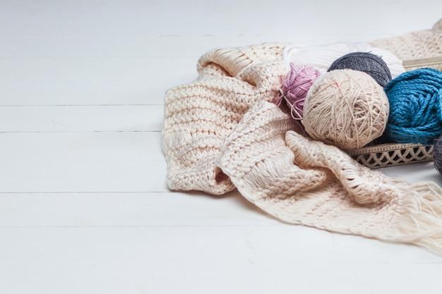 Las bolas de lana sobre una superficie de madera blanca. Foto gratis