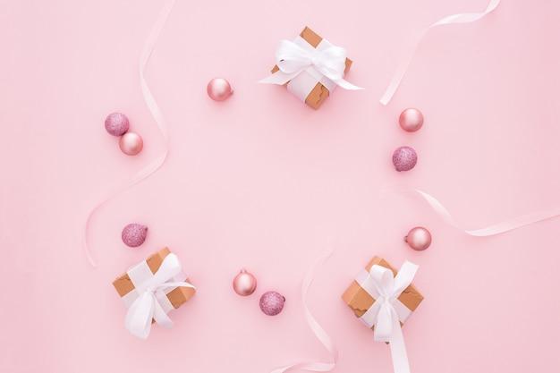 Bolas de navidad y regalos sobre un fondo rosa Foto gratis
