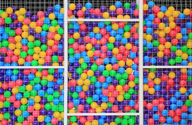Bolas plásticas coloridas en jaula en el patio de los niños. Foto Premium