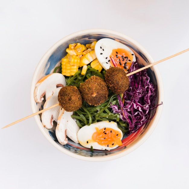 Bolas de pollo frito en el palo sobre el tazón con setas; maíz; huevo; ensalada de col y algas marinas Foto gratis