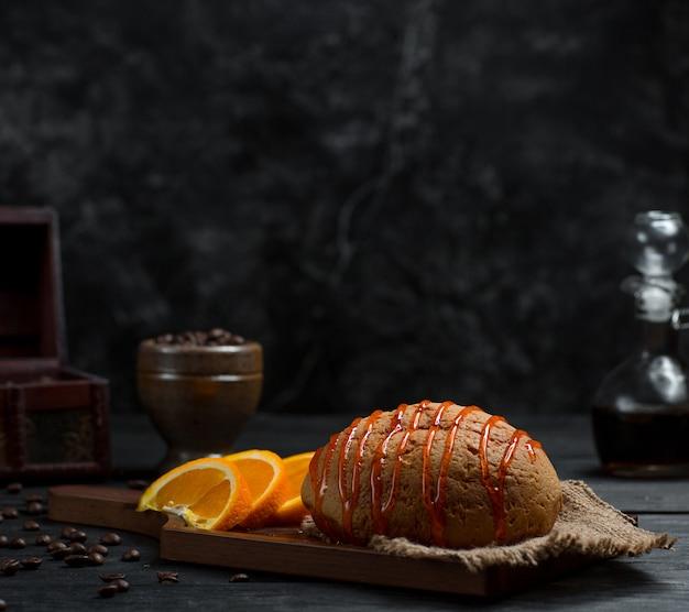 Bollo dulce con sirope de cereza y fruta de naranja en rodajas Foto gratis