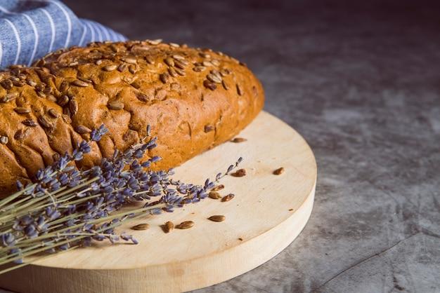 Bollo de trigo integral en la tabla de cortar Foto gratis