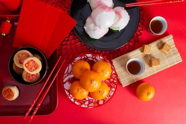 Bollos al vapor, naranjas, sartenes y té para el festival del año nuevo chino Foto Premium