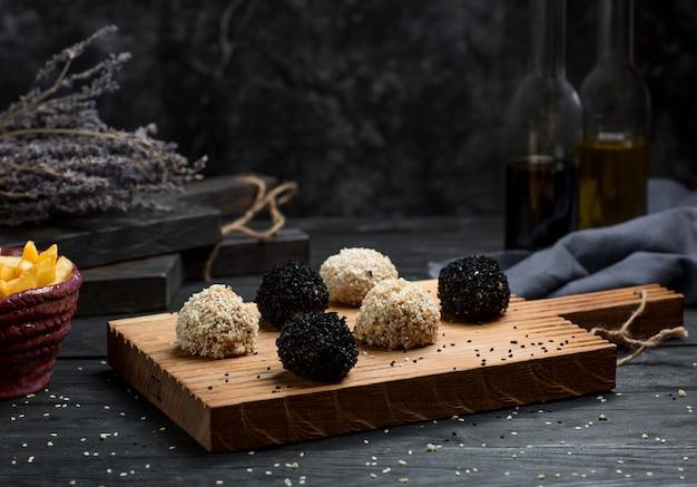 Bollos de chocolate cubiertos con trufas en una tabla de madera Foto gratis