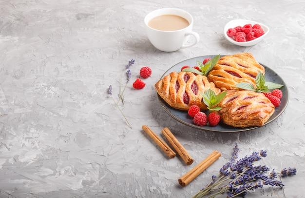 Bollos de hojaldre con mermelada de fresa en placa de cerámica azul sobre fondo de hormigón gris Foto Premium