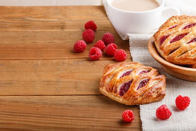 Bollos de hojaldre con mermelada de fresa sobre fondo de madera con lino textil y una taza de café Foto Premium