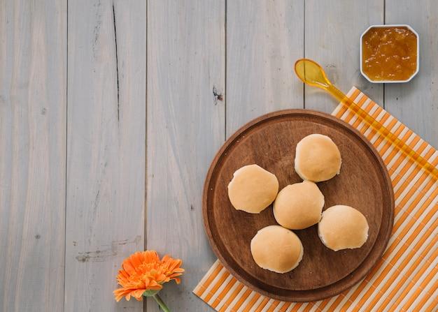Bollos pequeños sobre tabla de madera con mermelada Foto gratis