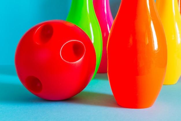 Bolos y pelota para jugar en los bolos de los niños sobre un fondo azul con espacio de copia Foto Premium