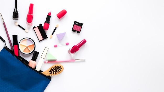 Bolsa de belleza con diferentes cosméticos en la mesa. Foto gratis