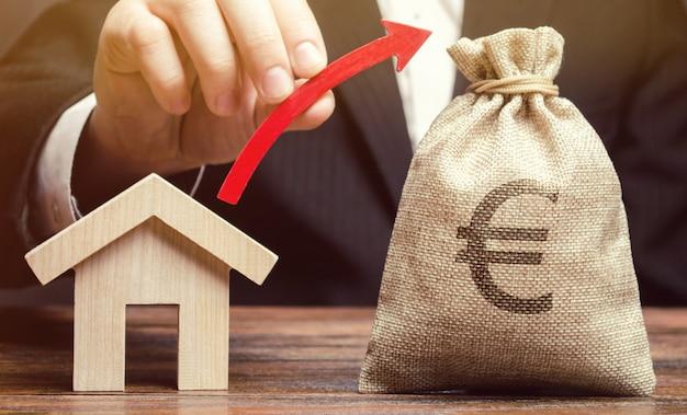 Una bolsa de dinero y una flecha roja en las manos. Foto Premium