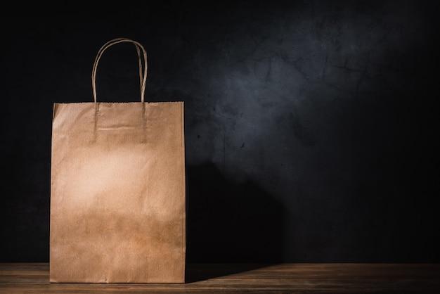 Bolsa de papel artesanal en mesa de madera Foto Premium