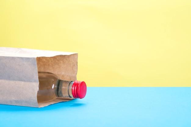 Bolsa de papel con una botella de alcohol en amarillo y azul. Foto Premium
