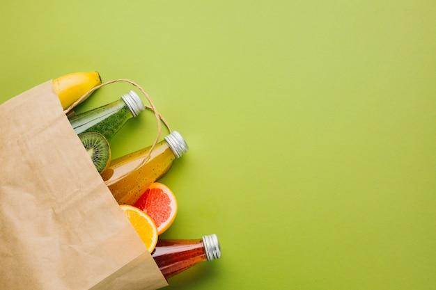Bolsa de papel flatlay con frutas y jugos. Foto gratis