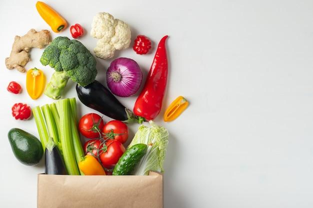 Bolsa de papel con las verduras en el fondo blanco. Foto Premium