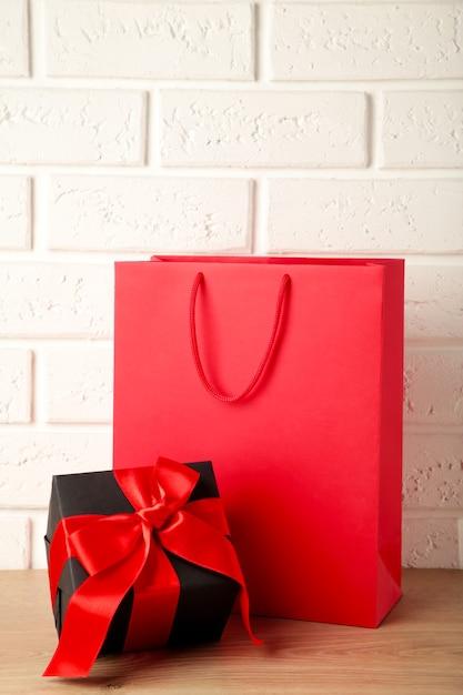 Bolsa roja con regalo sobre fondo claro. viernes negro. vista superior Foto Premium