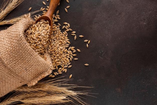 Bolsa de semillas de trigo y cuchara de madera. Foto gratis