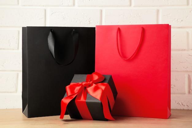 Bolsas de compras negras y rojas con regalo sobre fondo claro. viernes negro. vista superior Foto Premium