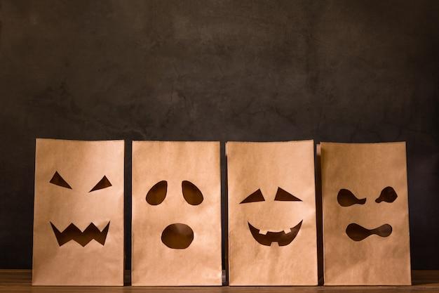 Bolsas de papel con cara de miedo en mesa de madera Foto Premium