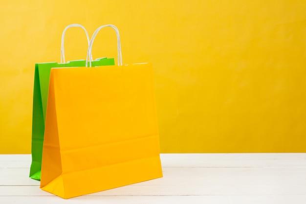 Bolsas De Papel Sobre Fondo Amarillo Brillante Foto Premium