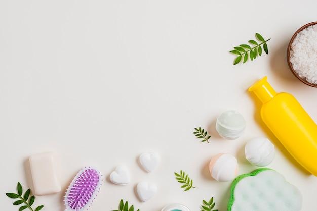 Bomba de baño jabón en forma de corazón; sal y cepillo para el pelo con una botella de cosméticos sobre fondo blanco Foto gratis