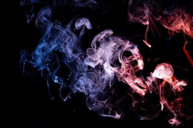 Bomba de humo azul y rojo sobre negro aislado Foto Premium
