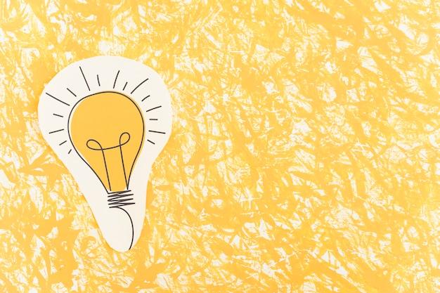 Bombilla dibujada mano recortada sobre el fondo amarillo Foto gratis