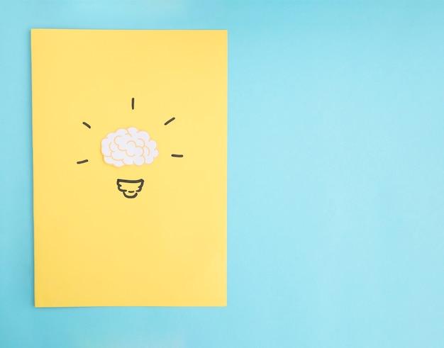 Bombilla de idea de cerebro en papel amarillo sobre el fondo azul Foto gratis