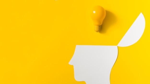 Bombilla de luz amarilla sobre el papel abierto recortar la cabeza contra el fondo de color Foto gratis