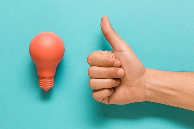 Bombilla y mano mostrando pulgar arriba Foto gratis