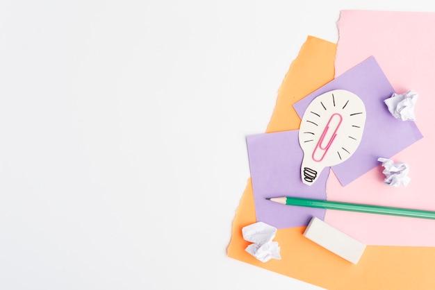 Bombilla de recorte de papel con útiles escolares sobre fondo blanco. Foto gratis