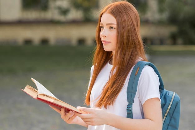 Bonita adolescente caminando por el campus universitario Foto gratis
