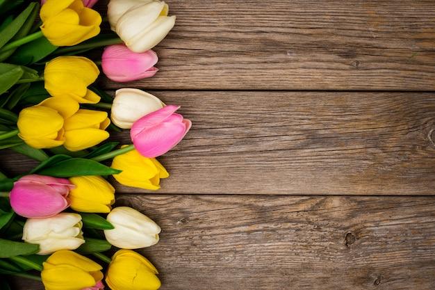 Bonita composición con tulipanes con espacio de copia en madera Foto gratis