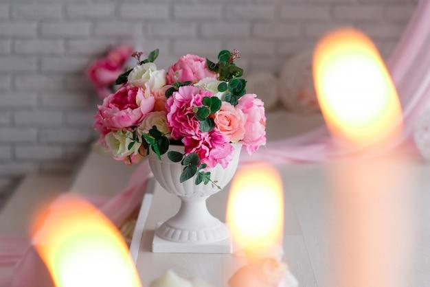 Bonita decoración en blanco y rosa. peonías y velas encendidas sobre un fondo claro. Foto Premium