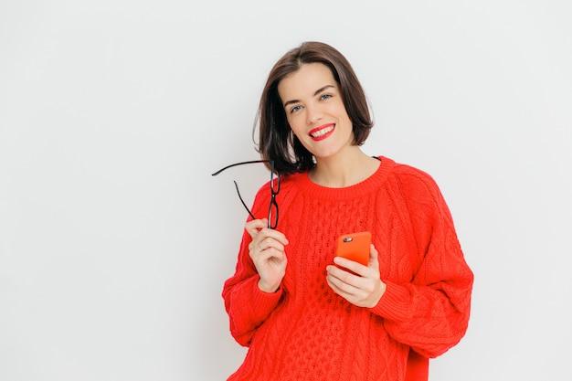 Bonita mujer con cabello corto y oscuro, usa un suéter rojo de invierno de gran tamaño, tiene gafas y teléfono inteligente Foto Premium