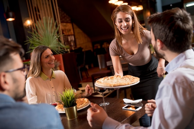 Bonita mujer camarero sirviendo a un grupo de amigos con comida en el restaurante Foto Premium